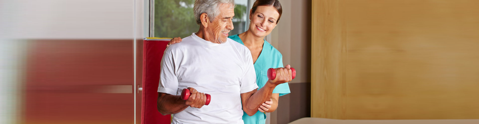 physiotherapist assisting senior man exercising with dumbbells