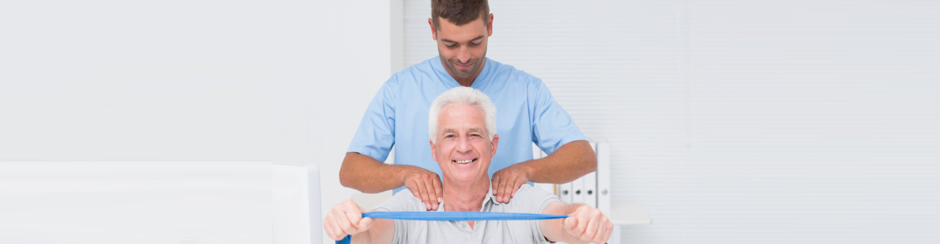 male physical therapist assisting senior man in exercising with resistance band
