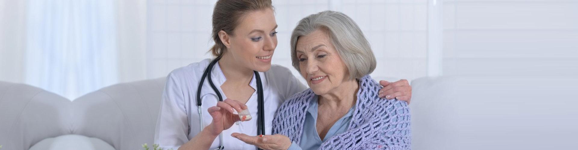 caregiver giving medicine to senior woman